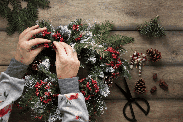 top-view-hands-decorating-christmas-wreath
